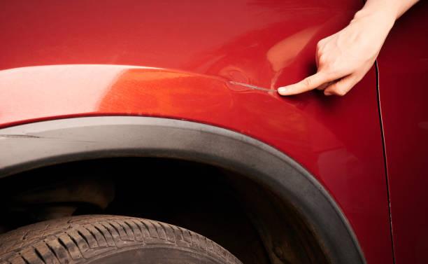 Hand zeigt auf Delle auf rotes Auto – Foto