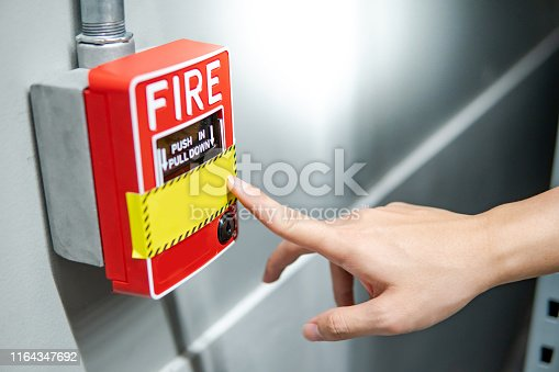Male hand pointing at red fire alarm switch on concrete wall in factory. Industrial fire warning system equipment for emergency.
