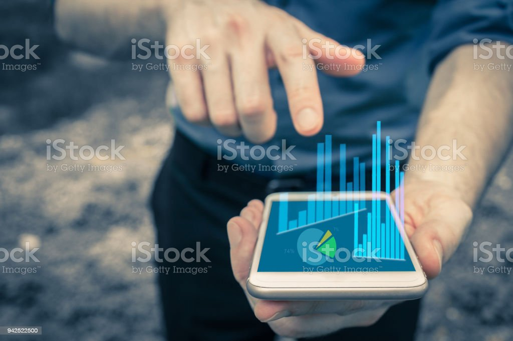 Hand pointing at mobile device for business use and charting data with bar charts and pie chart and valueable information on the company financial network. stock photo