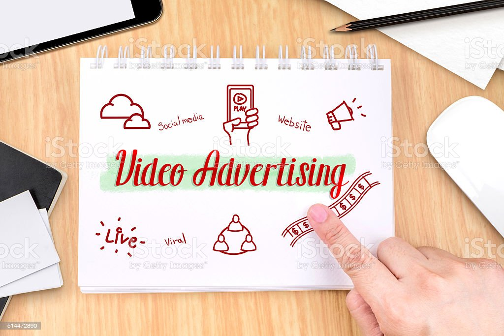 Hand pointing at Video Advertising on book with hand drawn stock photo