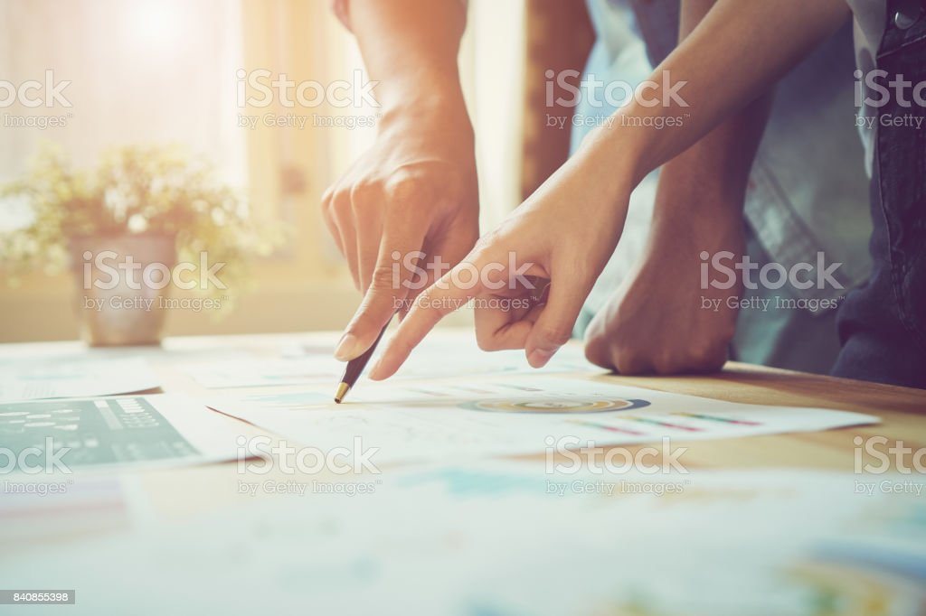 Hand pointing to a financial document on the desk. Between the agreed form of work to send customers. Teamwork ideas work best. stock photo