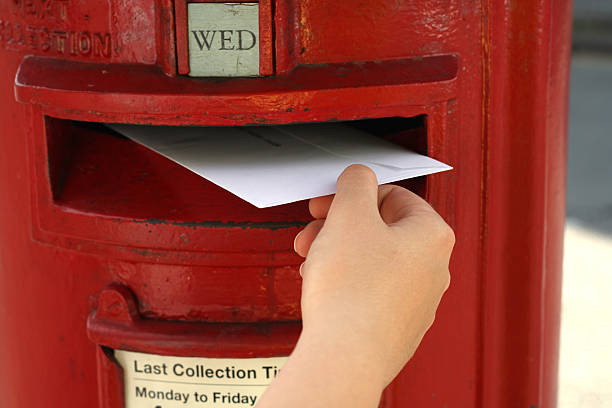 hand posting a  letter to red british postbox on street stock photo