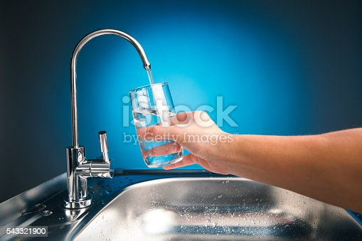 hand pouring a glass of water from filter tap, blue background