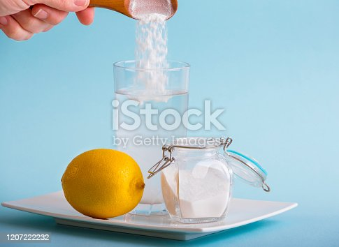 Hand pouring baking soda in drinking glass with water and lemon juice, health benefits for digestive system concept. Blue background, copy space.