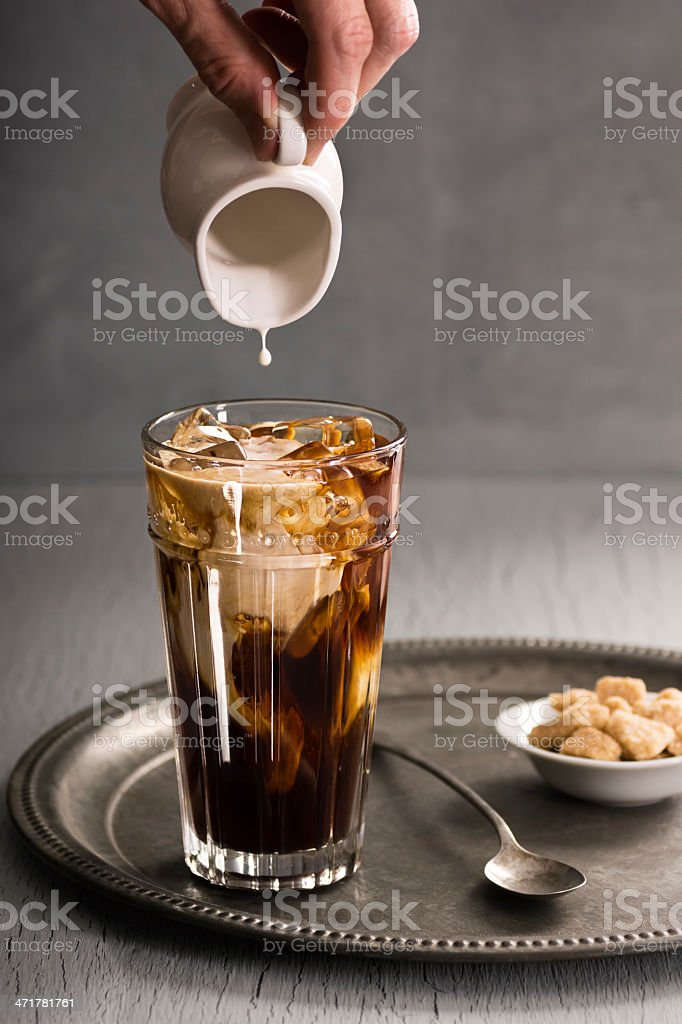Hand Pouring Cream Into Iced Coffee royalty-free stock photo