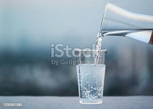Hand pouring drink water from bottle into glass with blurred city background