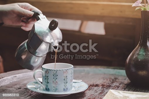 istock Hand pouring hot coffee into a cup on wooden table in coffee shop 935983310
