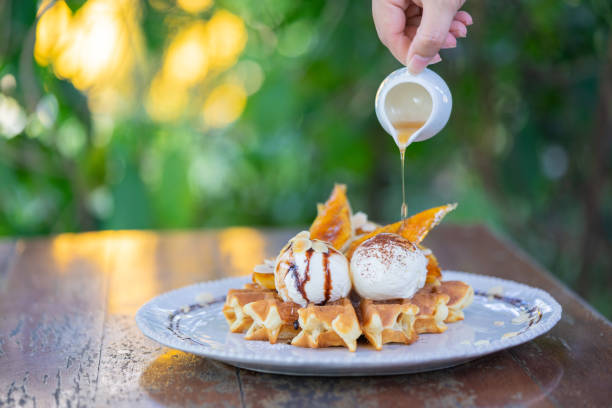 Hand pouring maple syrup on fresh waffles with ice cream on a wooden background stock photo