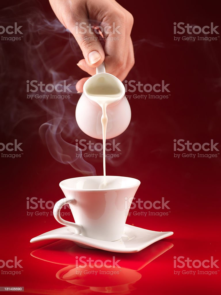 hand pouring milk in coffee cup royalty-free stock photo