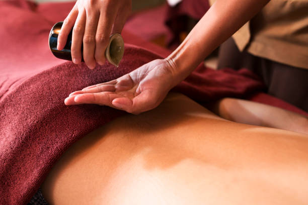 hand pouring oil for massage in spa - thai massage stock photos and pictures