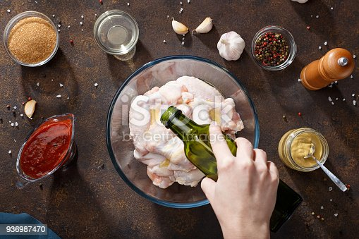 istock Hand pouring oil over raw chicken wings in glass bowl. 936987470