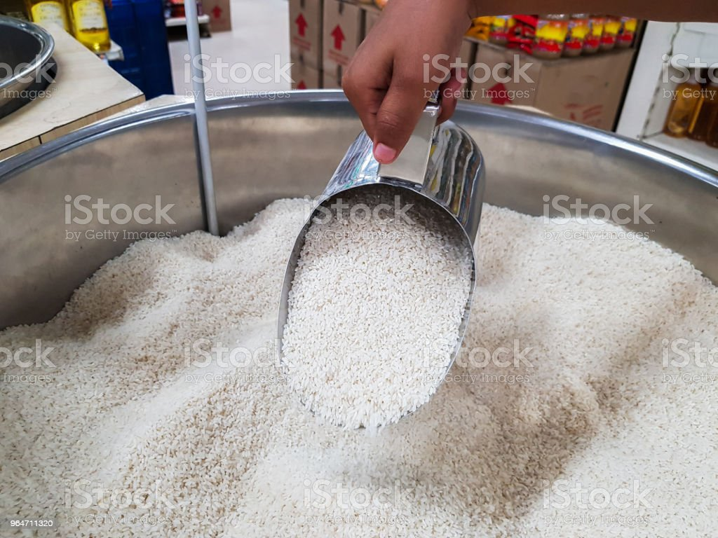 hand pouring raw uncooked heap of rice with measuring mug dispensing container at supermarket for sale royalty-free stock photo