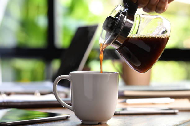 A hand pouring steaming coffee in to a cup on a work desk when work from home A hand pouring steaming coffee in to a cup on a work desk when work from home caffeine stock pictures, royalty-free photos & images