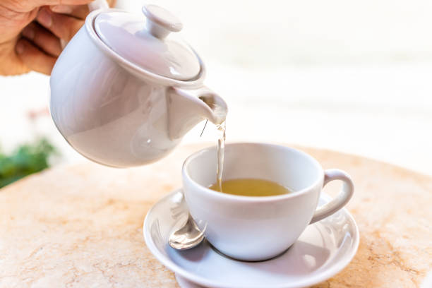 Hand pouring tea in outdoor cafe restaurant in white cup in summer in garden terrace on sunny day with porcelain teapot stock photo
