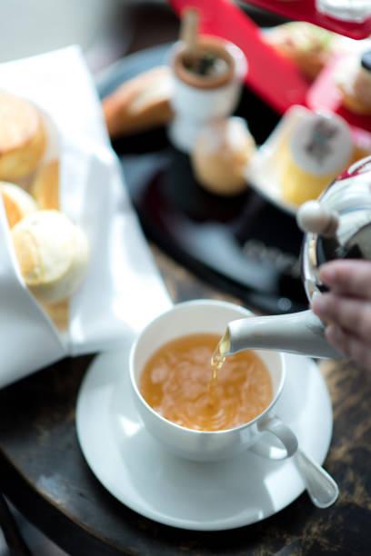 hand gießen tee in eleganz weißem porzellan keramik teetasse mit scones und nachmittags tee oder tee dessert-hintergrund. - darjeeling tee stock-fotos und bilder