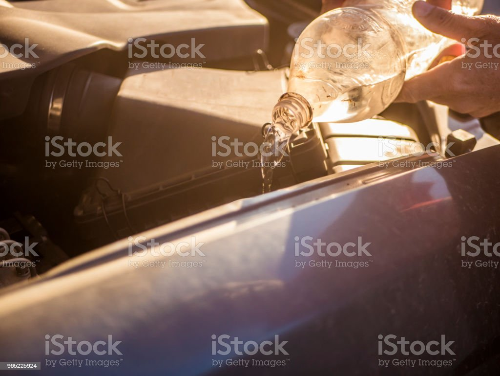hand pouring water in the car motor repairing royalty-free stock photo
