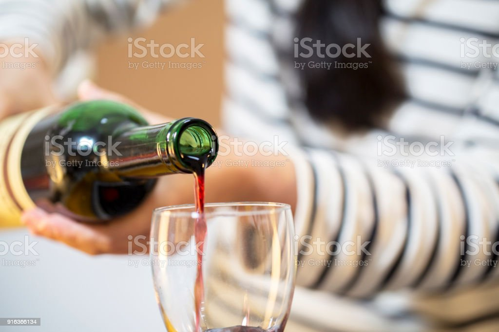 hand pouring wine into glass stock photo