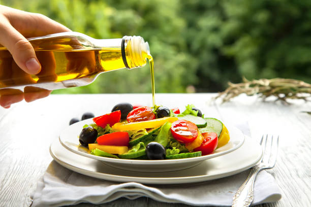 Hand pours olive oil in a plate with fresh summer salad in the background natural mode. preparation of summer salad. Hands in the frame pour from a glass bottle of olive oil on the salad salad dressing stock pictures, royalty-free photos & images