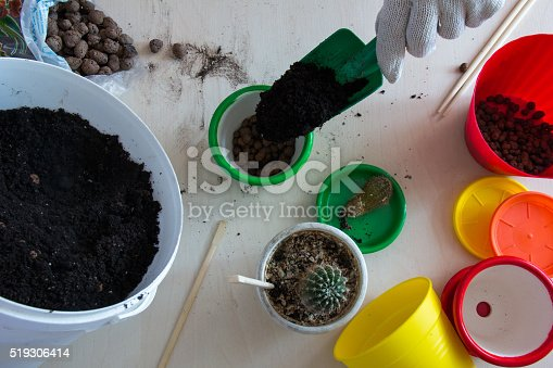 Hand pours the ground in a green pot top view