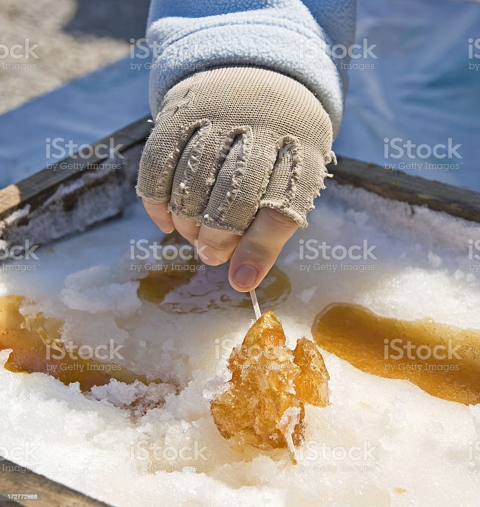 Hand preparing maple syrup treat on fresh snow royalty-free stock photo