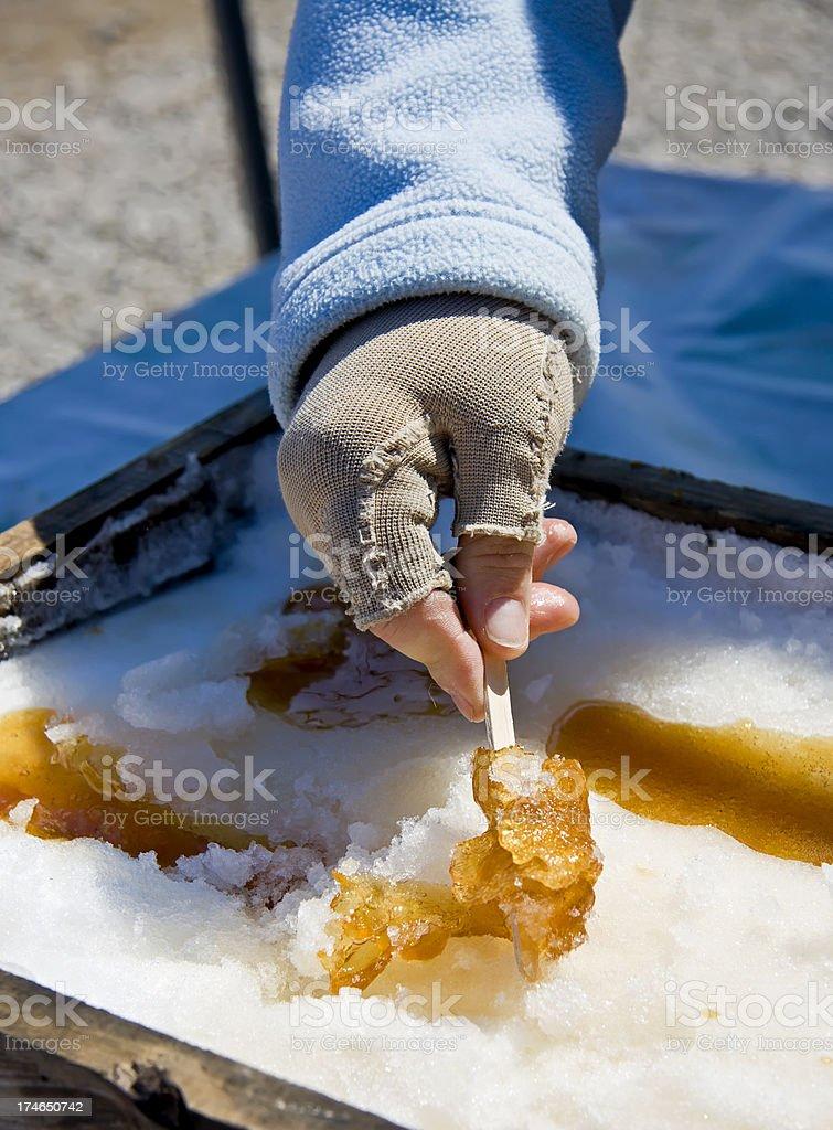 Hand preparing maple syrup treat on fresh snow royalty-free stock photo