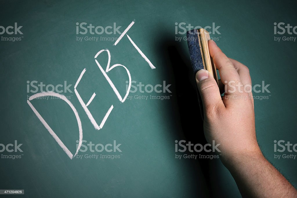 Hand preparing to erase the word DEBT from a chalkboard royalty-free stock photo