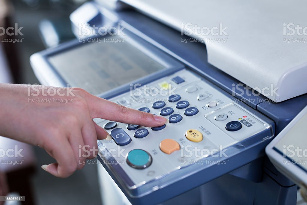 hand press button on panel of printer stock photo