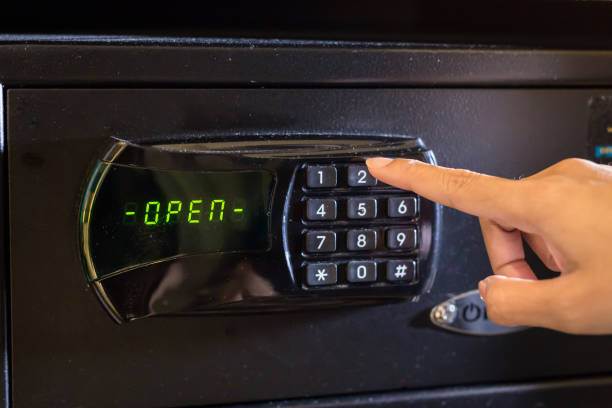 Hand press key on black safety box with open status - foto stock