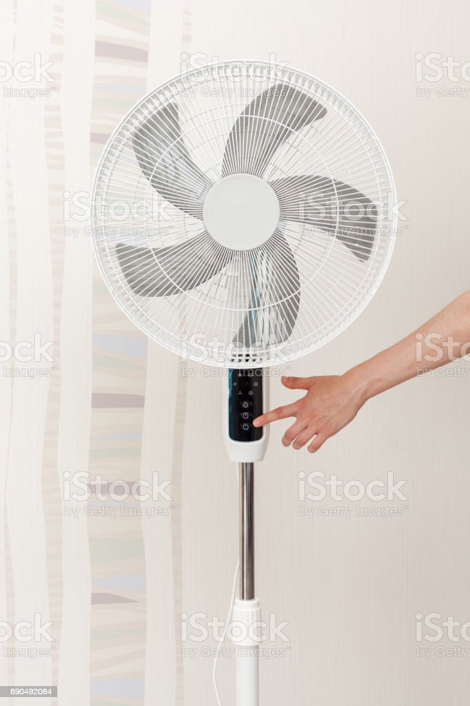 Hand presses the button on the control panel on the white electric fan Concept : Save Energy, Save World, Save money, Selective focus. stock photo