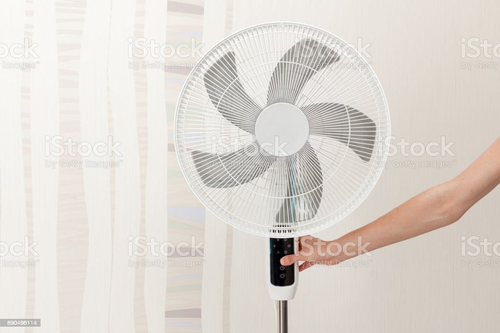 Hand presses the button on the control panel on the white electric fan stock photo