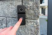 istock Hand pressing button of video intercom 1254846448