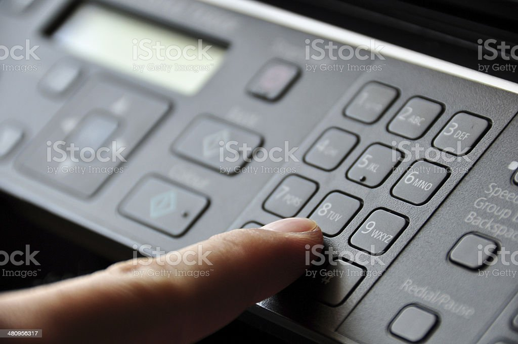 Hand pressing button on copy machine stock photo