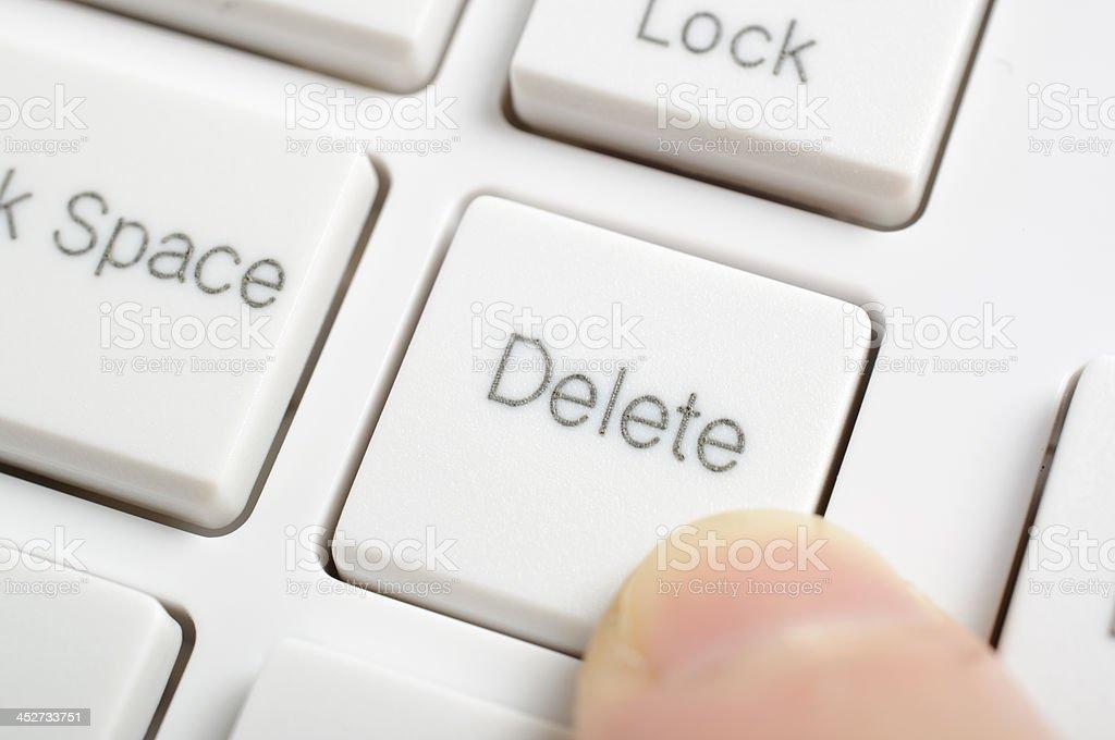 Hand pressing delete key stock photo