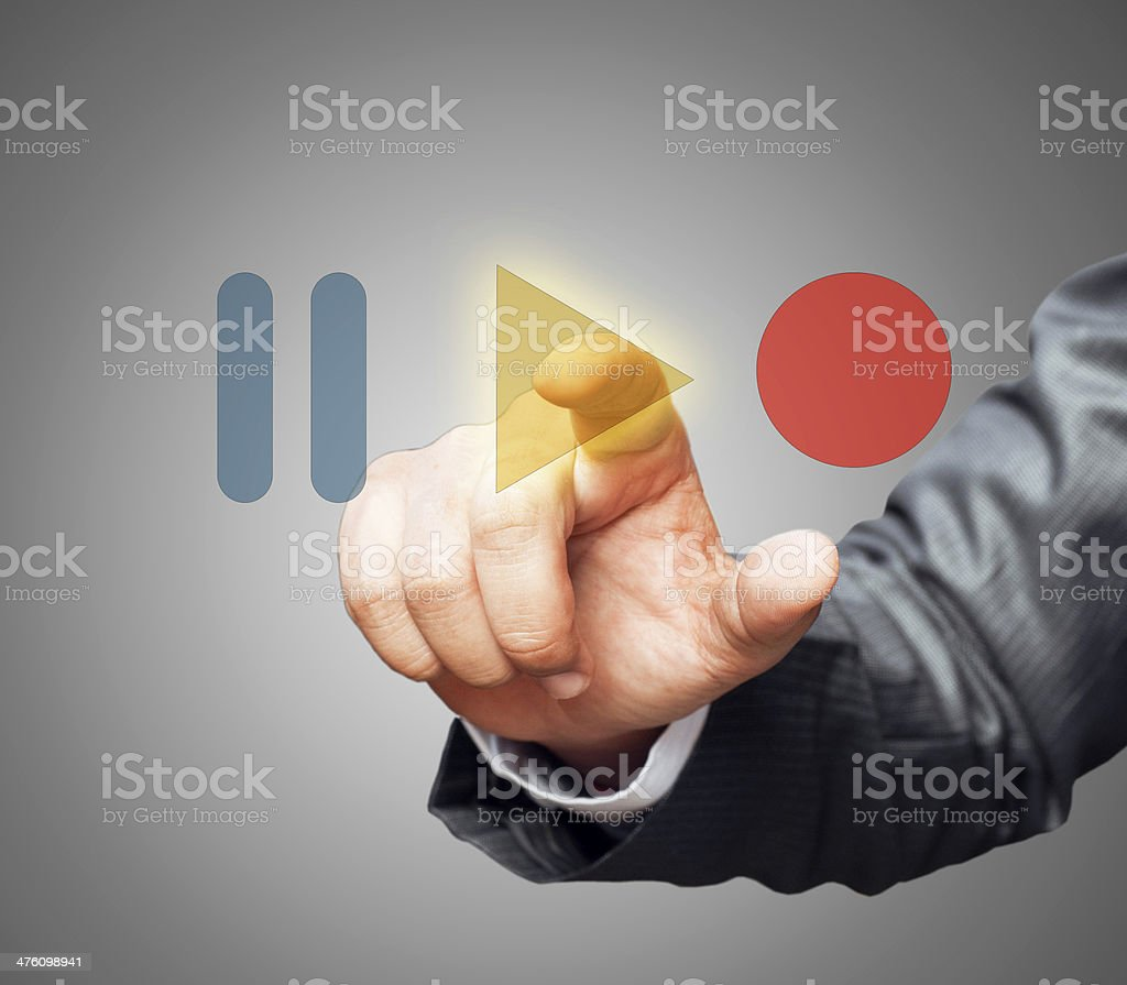 Hand pressing play button stock photo