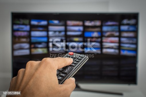 istock Hand pressing remote of smart tv 1013520894