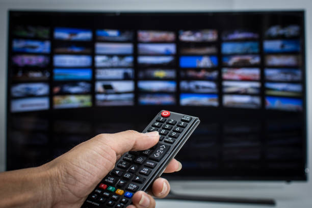 Hand pressing remote of smart tv stock photo