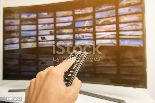 istock Hand pressing remote of smart tv 1013520978