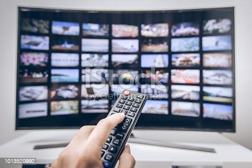 istock Hand pressing remote of smart tv 1013520992