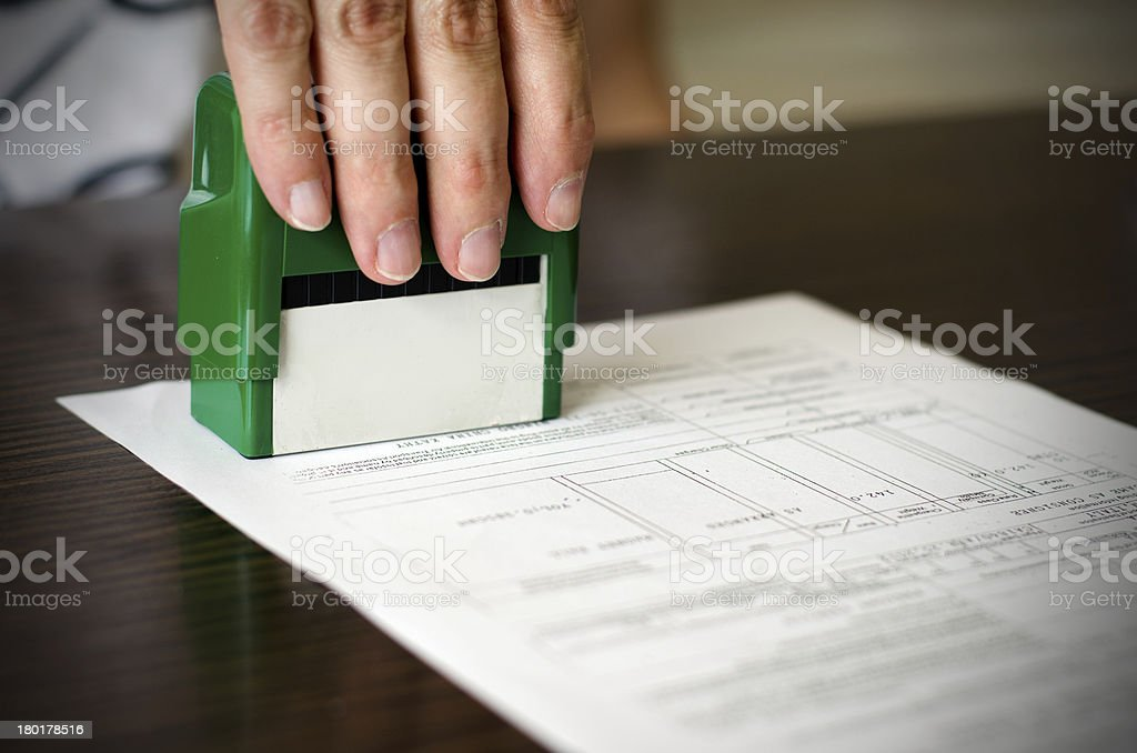 Hand pressing rubber stamp on document royalty-free stock photo
