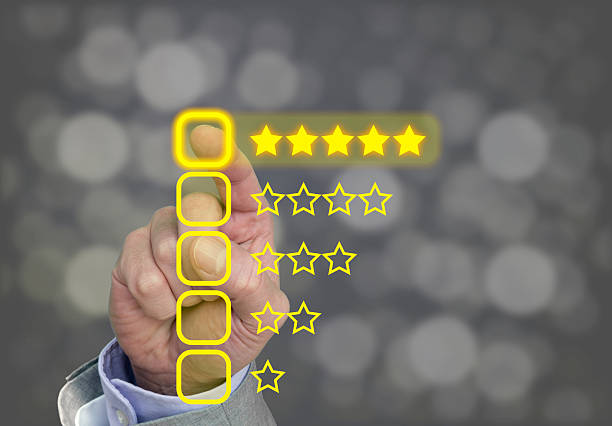 Hand pressing yellow five star button of performance rating stock photo