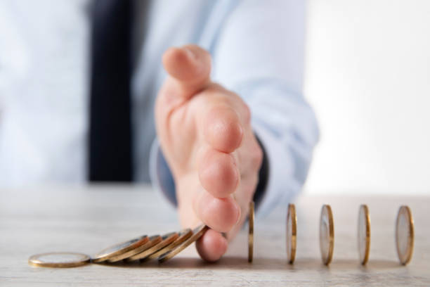 Hand Protecting Coins From Falling stock photo