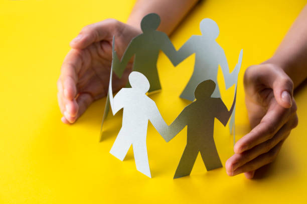 Hand Protecting Paper Cut Out Figure stock photo