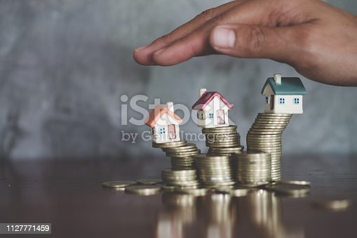 istock Hand protection, house model on top of stack of money as growth of mortgage credit, Concept of property management. Invesment and Risk Management, Copy space 1127771459