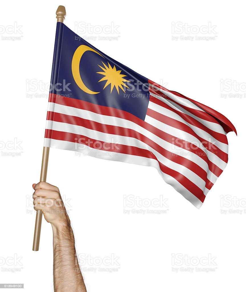 Mão orgulhosamente acenando a bandeira nacional da Malásia - foto de acervo