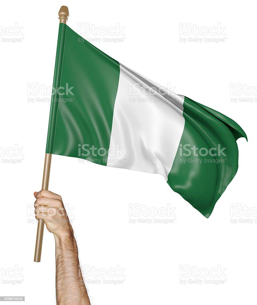 Agitando la mano con orgullo nacional bandera de Nigeria, representación en 3D - foto de stock