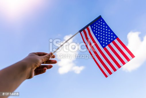 514069232istockphoto Hand proudly waving the national flag of the United States 813114418