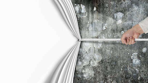 hand pulling blank curtain covered old dirty mottled concrete wa stock photo