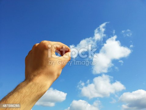 istock Hand pulling cloud with copyspace 487586285