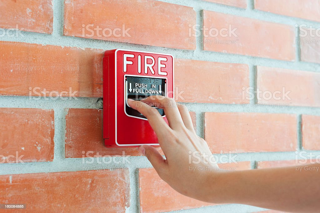 Hand pulling down fire alarm on brick wall royalty-free stock photo