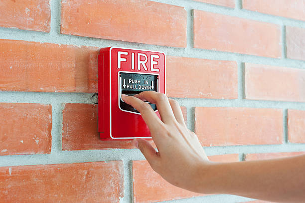 Hand pulling down fire alarm on brick wall stock photo